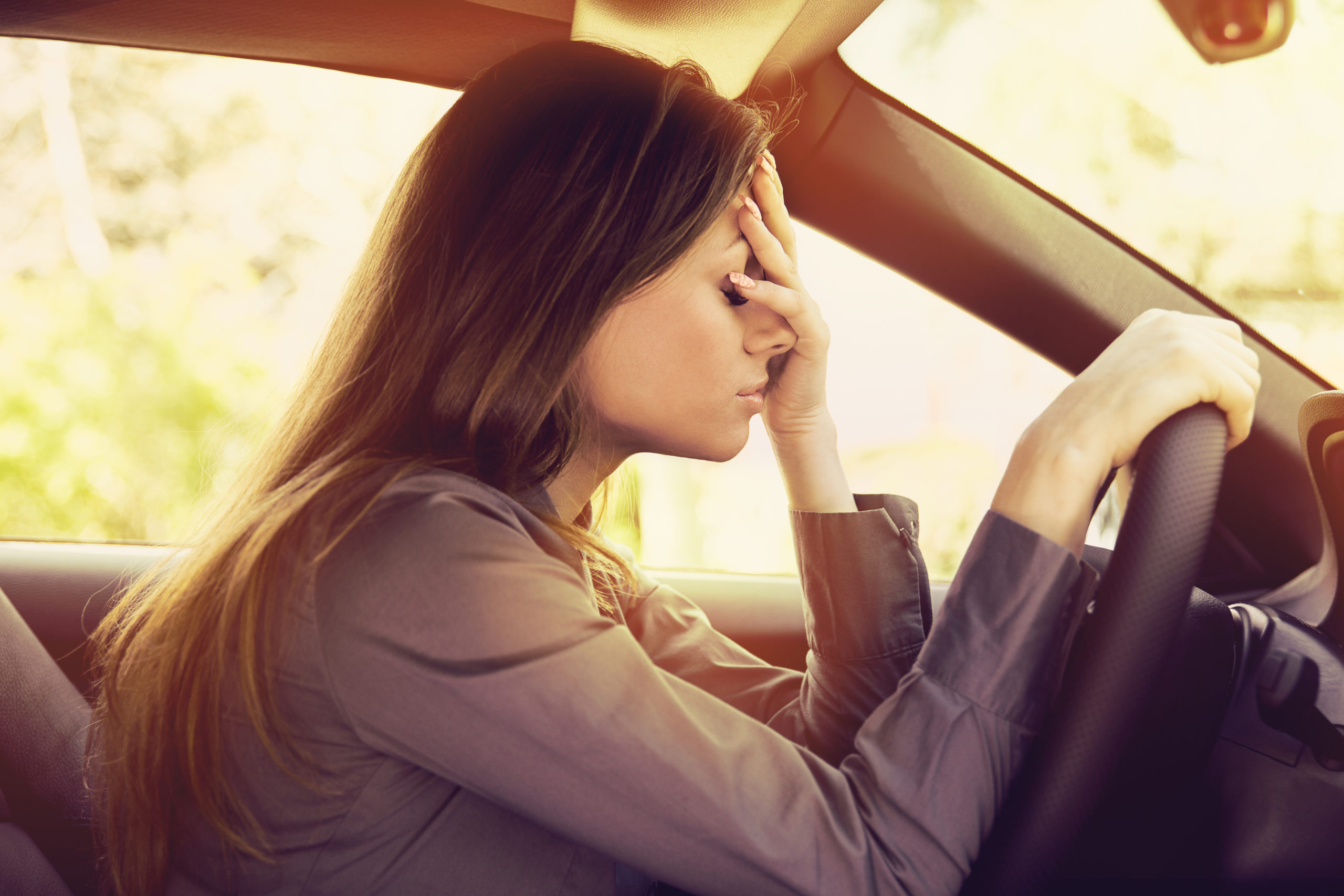 woman driving not feeling well