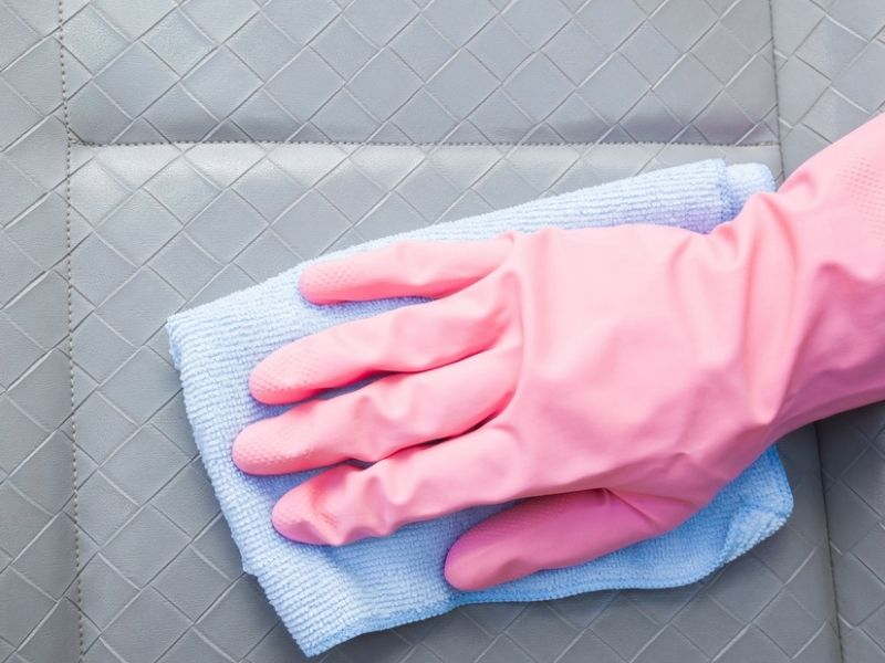 hand in gloves with cleaning cloth cleaning vehicle seat