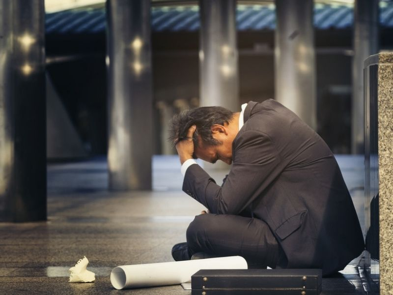 stressed man in business attire sitting on the floor